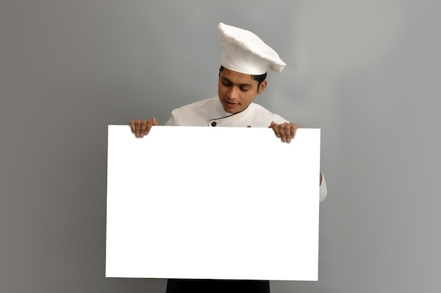 Happy male chef dressed in uniform holding white advertising banner looking on board