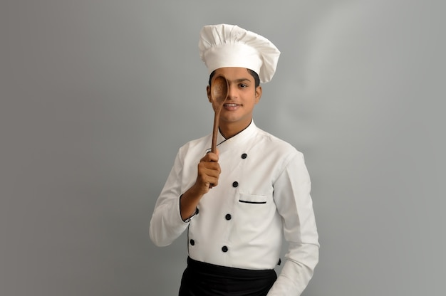 Happy male chef dressed in uniform holding wooden spoon on one eye