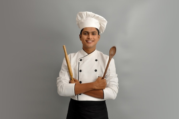 Happy male chef dressed in uniform holding wooden spoon and roller in crossed arms
