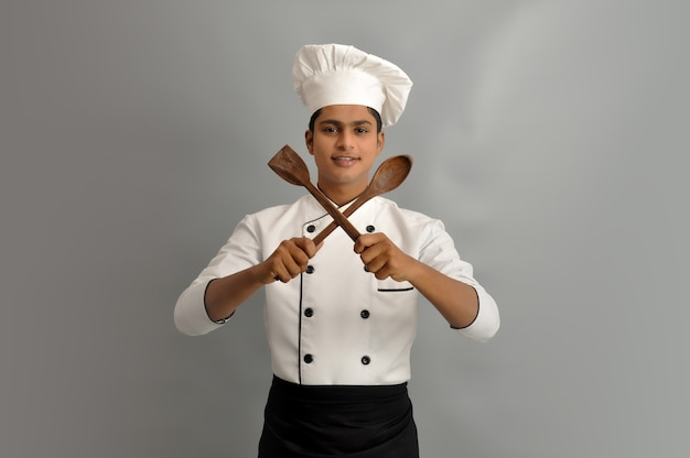 Happy male chef dressed in uniform holding wooden spoon