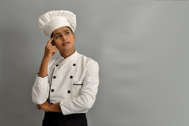 Happy male chef dressed in uniform thinking daydreaming or doubting looking to the side