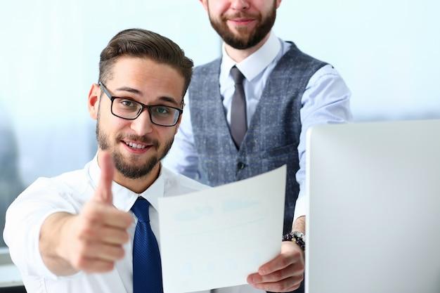 Счастливые коллеги-мужчины радуются успеху на работе