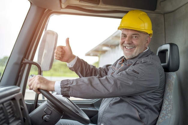 Happy male construction worker doing the thumbs-up gesture in a truck under the sunlight