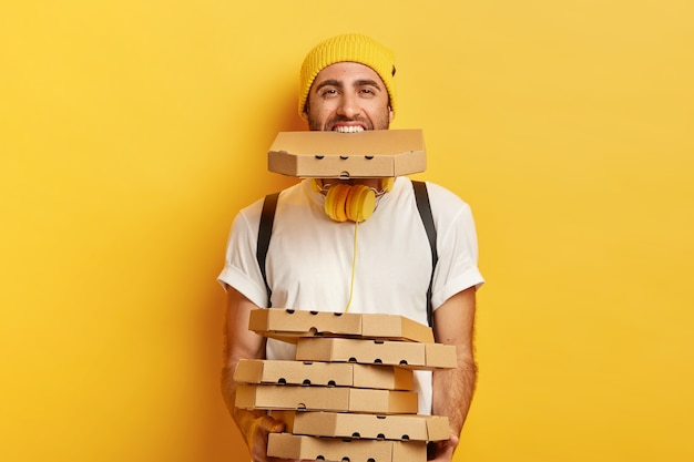 Happy male courier overloaded with carton pizza boxes, holds stack of cardboard containers and one in mouth, dressed in casual wear, isolated over yellow wall