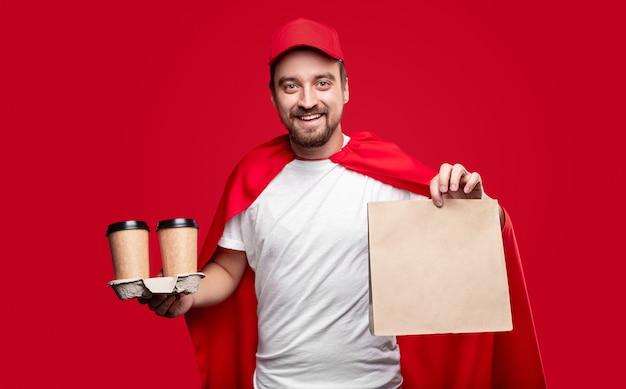 ビジネスランチを提供しながら紙袋と使い捨てカップを示す赤いマントとキャップの幸せな男性配達人