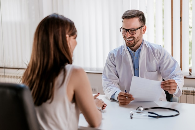 Happy male doctor discussing with patient at table in clinic