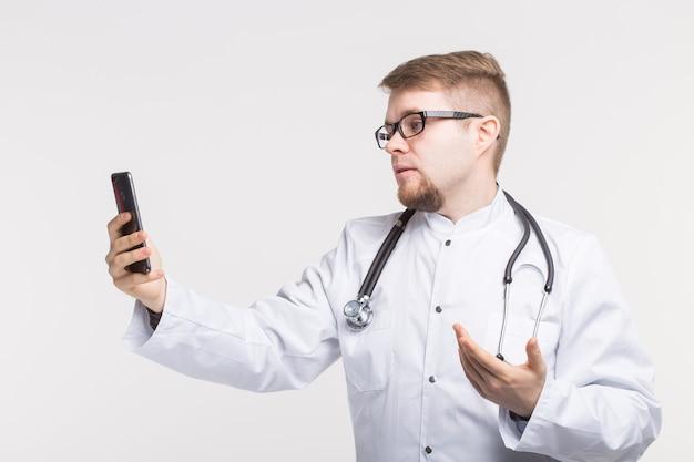 Счастливый мужской доктор делает селфи фото со смартфоном на белом фоне