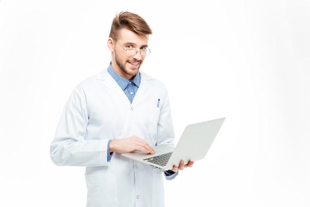 白い背景で隔離のラップトップコンピューターを使用して幸せな男性医師