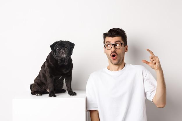 かわいい黒いパグの近くに座って、驚いて驚いた顔、白い背景を持つペットを見て幸せなオスの犬の飼い主