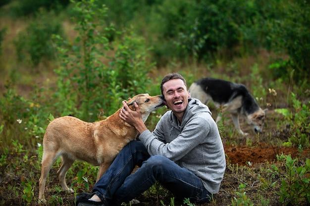 地面に座って、犬のなめる顔を混ぜながら笑っている幸せなオスの犬の飼い主