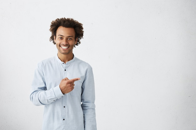 Happy male dressed in white shirt pointing with at blank wall