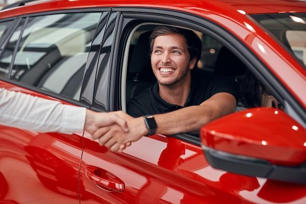 ディーラーと握手車で幸せな男性ドライバー