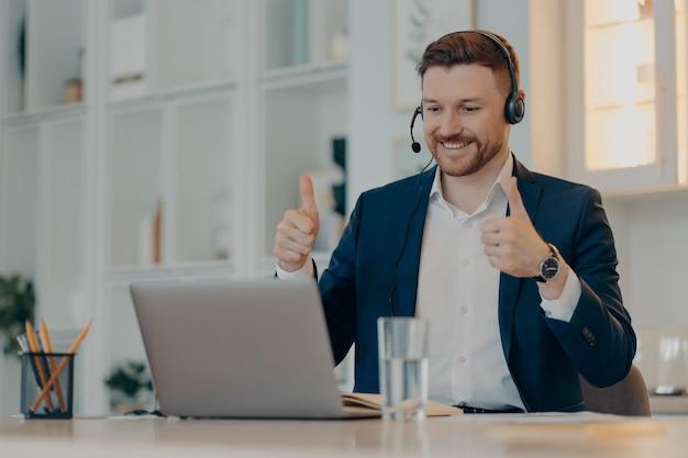 Счастливый служащий мужского пола соглашается, как жест держит палец вверх. довольный коллегой, бизнес-презентация, делает видеозвонок, использует наушники с микрофоном, носит официальную одежду. исполнительный работник