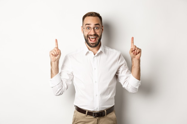 Happy male entrepreneur in business clothes, pointing fingers up and showing promo offer, standing over white background.