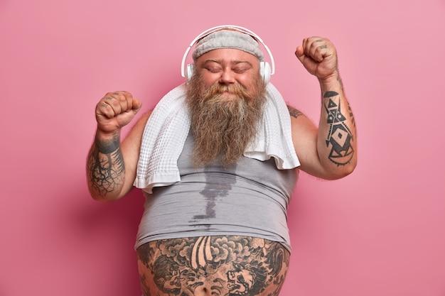 幸せな男性のfatsoは音楽でトレーニングを楽しんで、手を上げて踊り、汗をかいた体を持ち、首にシャツとタオルを着て、ピンクの壁に隔離されています。ぽっちゃりアスリートが素晴らしい結果を達成して幸せ