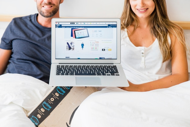 Happy male and female in bed showing laptop