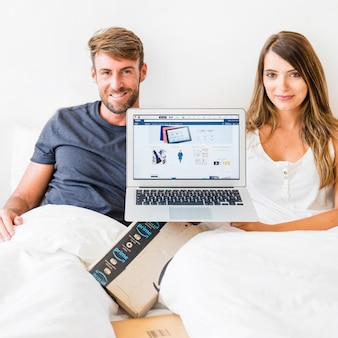 Happy male and female in bed with laptop