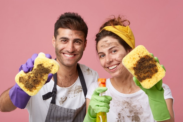 Happy male and female smiling broadly holding dirty sponges and washing spray being glad to wash furniture in house.