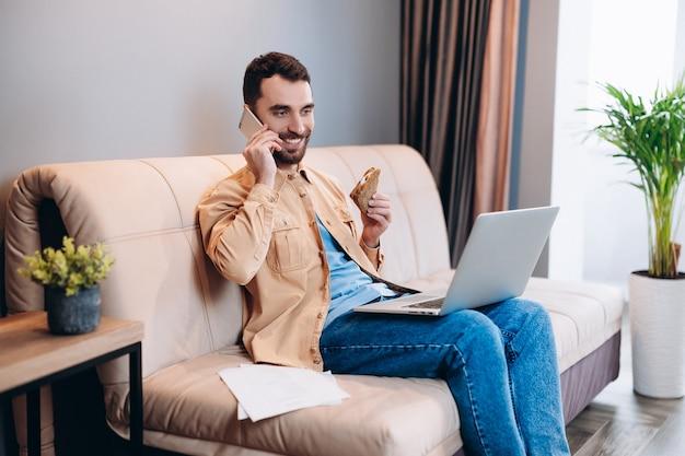 幸せな男性のフリーランサーは、彼のリビングルームのソファに座って、ラップトップ画面でタスクを見ている携帯電話を使用してクライアントと話します