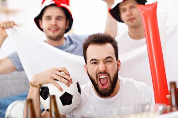 テレビでスポーツを応援し、見ている幸せな男性の友人