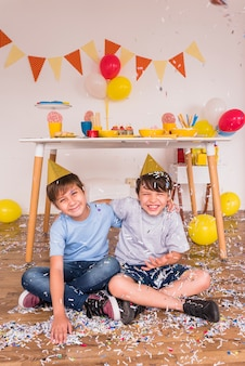 Happy male friends playing with confetti during birthday celebration