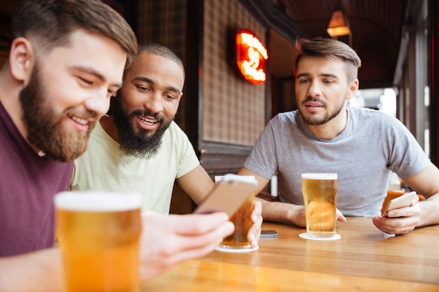 Happy male friends sitting at the table with beer and using smartphone in restaurant