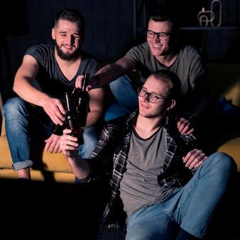 Счастливые друзья-мужчины вместе смотрят спорт по телевизору за пивом