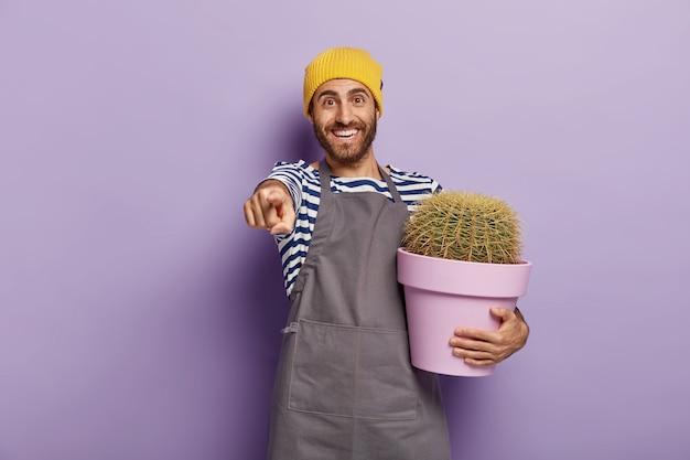 Felice giardiniere maschio tiene in mano un vaso di cactus, mostra qualcosa di fantastico a distanza, punta il dito indice, vestito con un'uniforme speciale