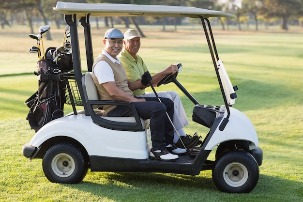 Happy male golfer friends sitting in golf buggy