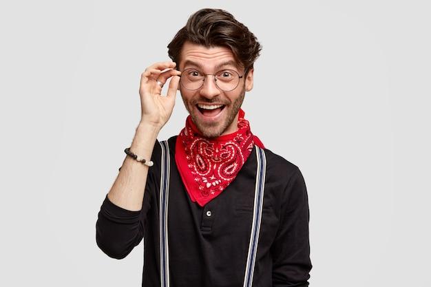 Felice hipster maschio essere contento, indossa occhiali e vestiti alla moda, ha un'espressione gioiosa, sta da solo contro il muro bianco. persone e stile