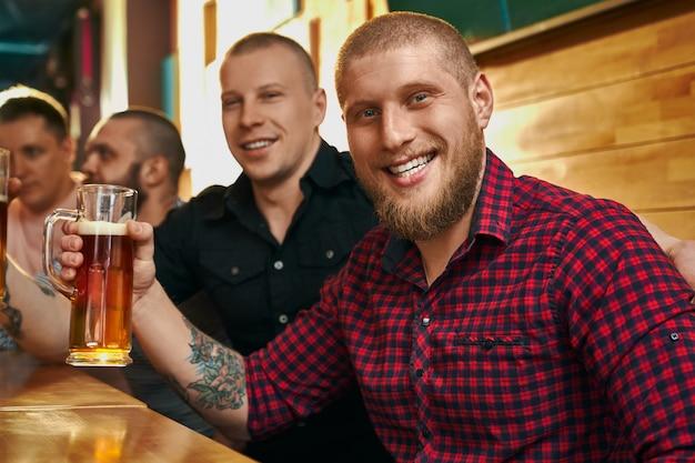 문신 맥주 잔을 유지, 카메라를보고 웃 고 카페에서 포즈와 함께 행복 한 남성 힙 스터. 친구와 함께 술을 마시고, 휴식하고 저녁을 즐기는 젊은 남자. 재미의 개념.