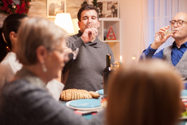 Happy male and his father drinking a glass of wine at christmas family dinner.
