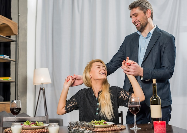 Happy male holding hands of cheerful female at table