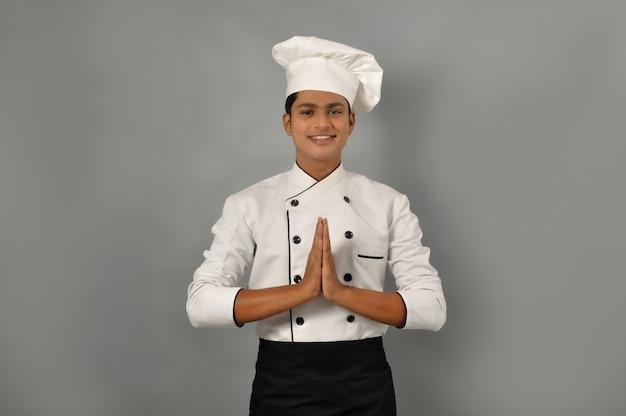 Счастливый индийский шеф-повар мужского пола в позе приветствия к намасте руки поварской профессии и концепции людей