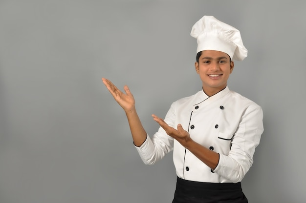 Happy male indian chef pointing with his hands on a grey wall