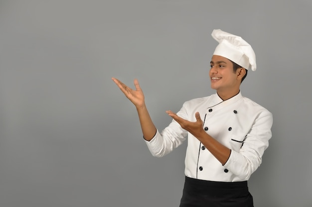 Happy male indian chef showing gesture with both hands over grey wall