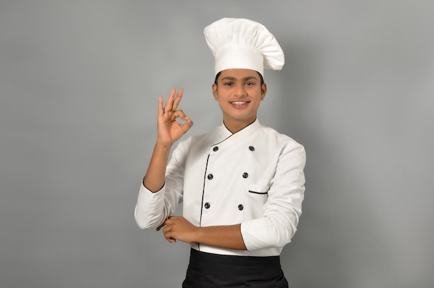 Happy male indian chef showing ok gesture with one hand
