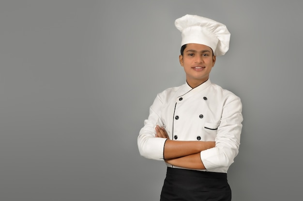 Happy male indian chef standing over grey wall