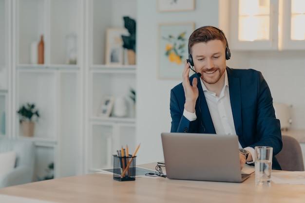 Счастливый мужчина-менеджер в костюме работает онлайн на компьютере и с помощью гарнитуры, сидя в гостиной и печатая на клавиатуре, бизнесмен работает удаленно из дома. концепция удаленной работы