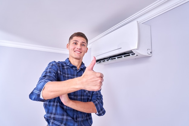 Счастливый мужчина-хозяин в синей рубашке установил кондиционер в помещении и доволен своей работой, показывает палец вверх и улыбается