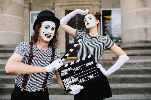 Happy male mime holding clapperboard in front of posing female mime