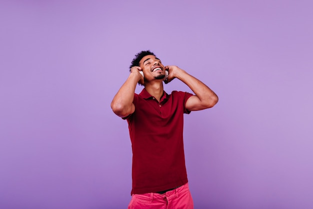 Happy male model listening music with eyes closed. indoor shot of laughing carefree man in red t-shirt posing in headphones.