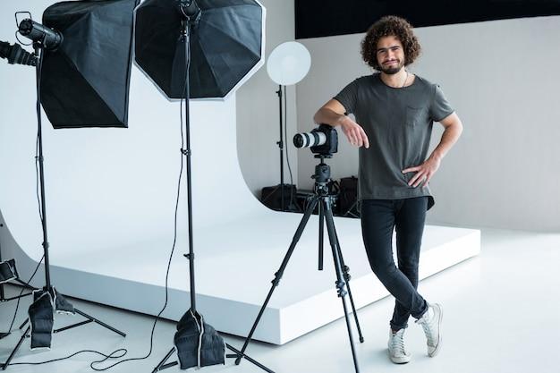 スタジオに立って幸せな男性カメラマン