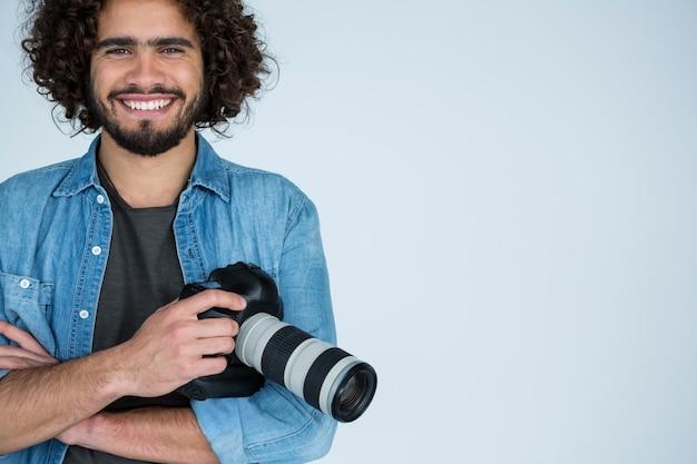 Счастливый мужской фотограф, стоя в студии