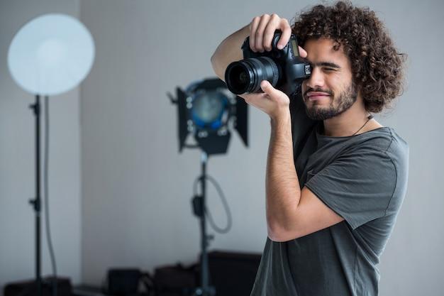 Счастливый мужской фотограф с цифровой камерой в студии