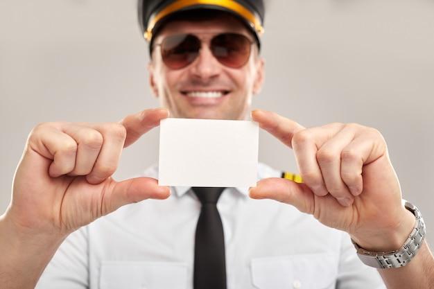 空白のカードを示す幸せな男性パイロット