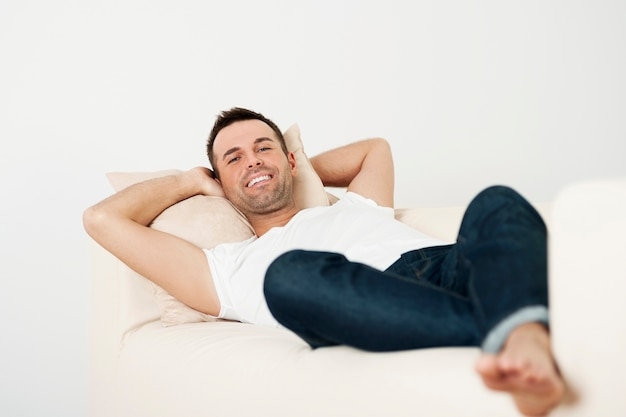 自宅のソファでリラックスして幸せな男性