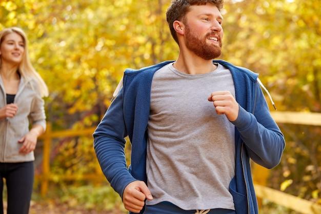 幸せな男性が森でジョギングを実行している、金髪の女性のガールフレンドがジョギング