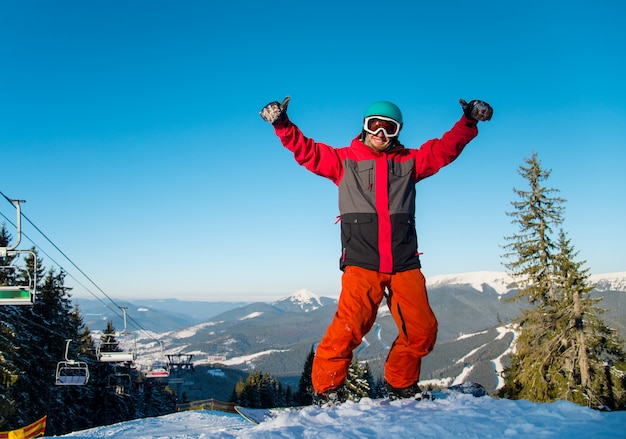 幸せな男性スノーボーダーが山の冬のスキーリゾートの雪の斜面に立って、親指を現して。スキー場のリフトと青い空