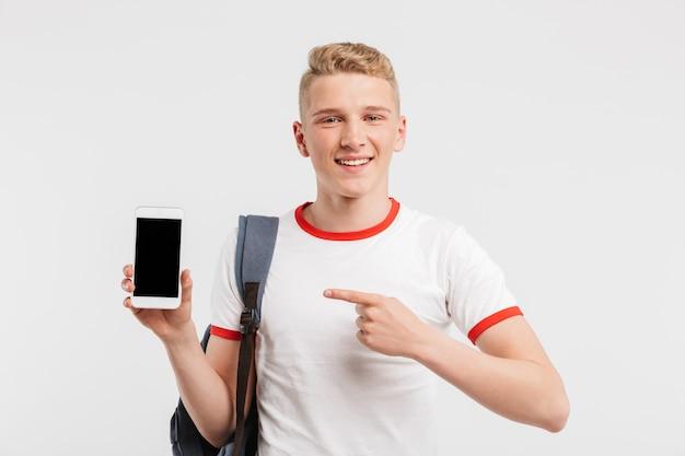 Счастливый мужчина студент, имеющий чистую здоровую кожу, носить рюкзак, указывая пальцем на черный экран copyspace смартфона, изолированных на белый